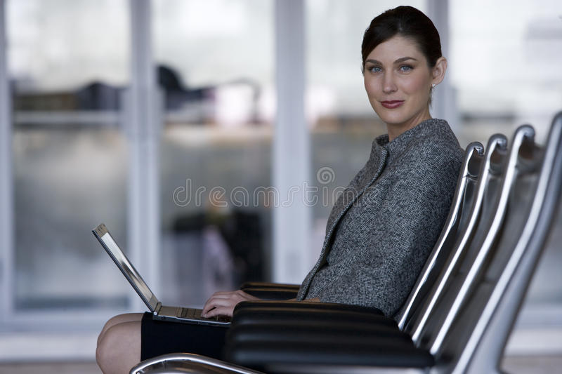 Businesswoman typing on laptop in airport waiting area stock image
