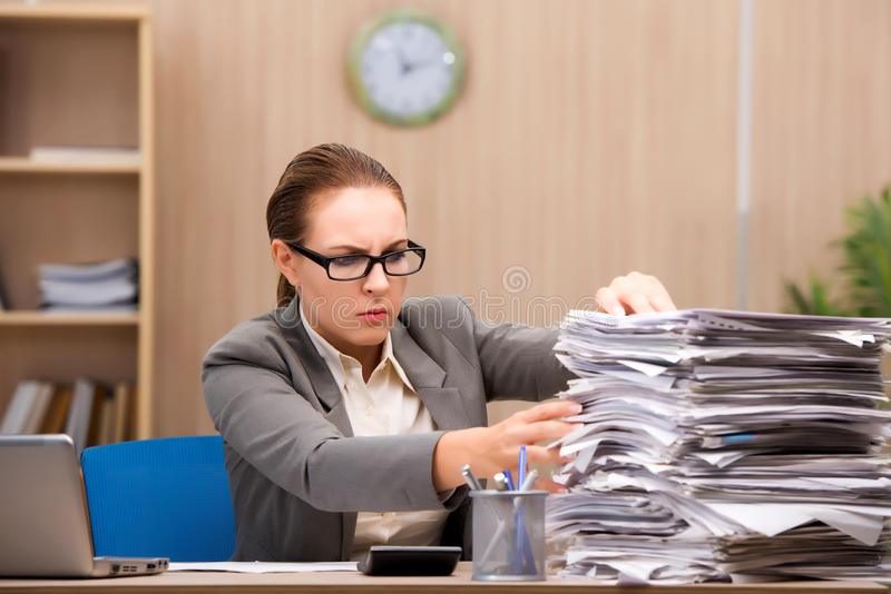 The businesswoman under stress from too much work in the office. Businesswoman under stress from too much work in the office stock images