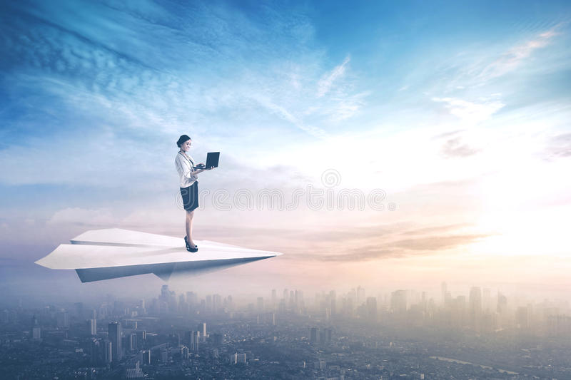 Businesswoman uses laptop on paper aeroplane. Young businesswoman standing on a paper aeroplane while using a laptop computer and flying above a city royalty free stock photo