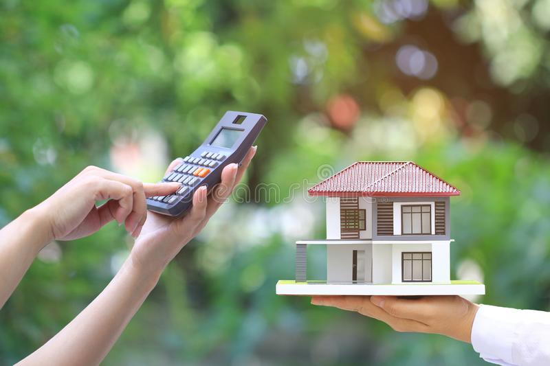 Businesswoman using a calculator and wooden house on green background, Accountants calculating profit and Interest rates concept royalty free stock photos
