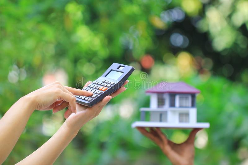 Businesswoman using a calculator and wooden house on green background, Accountants calculating profit and Interest rates concept.  royalty free stock photos