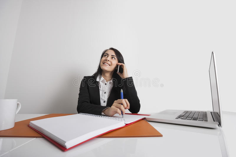 Businesswoman using cell phone at office desk stock image
