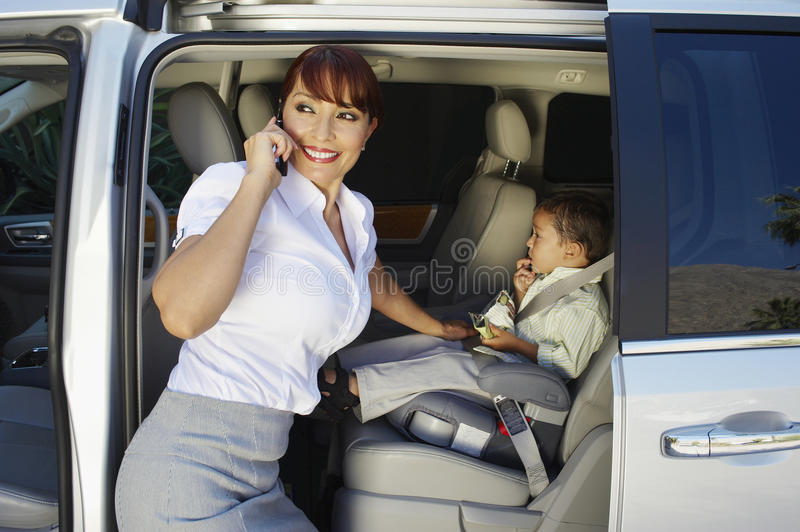 Businesswoman Using Cell Phone With Son Sitting In Car royalty free stock photography