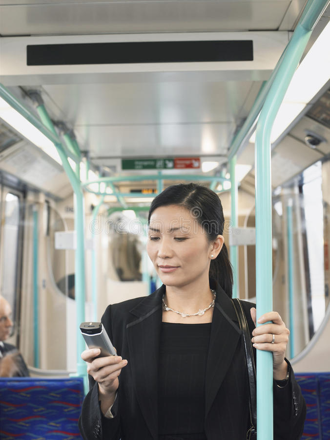 Businesswoman Using Cellphone In Train. Young Asian businesswoman using cellphone in the train stock photography