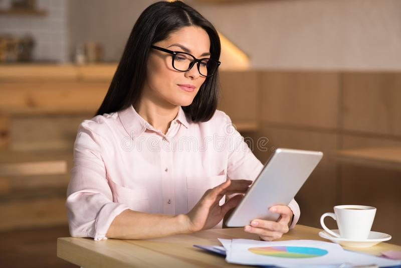 Businesswoman using digital tablet in cafe. Portrait of confident businesswoman wearing eyeglasses using digital tablet in cafe stock images