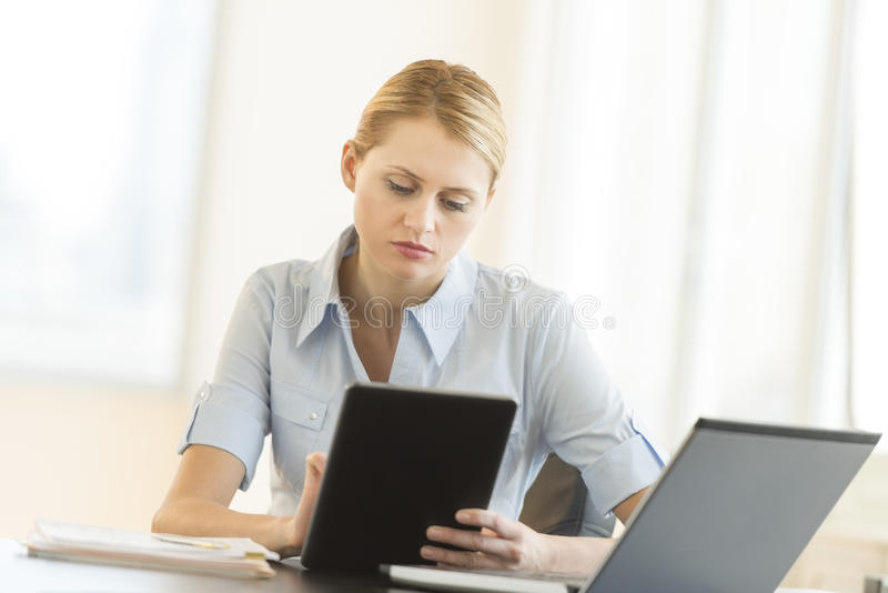 Businesswoman Using Digital Tablet While Sitting At Desk Royalty Free Stock Images