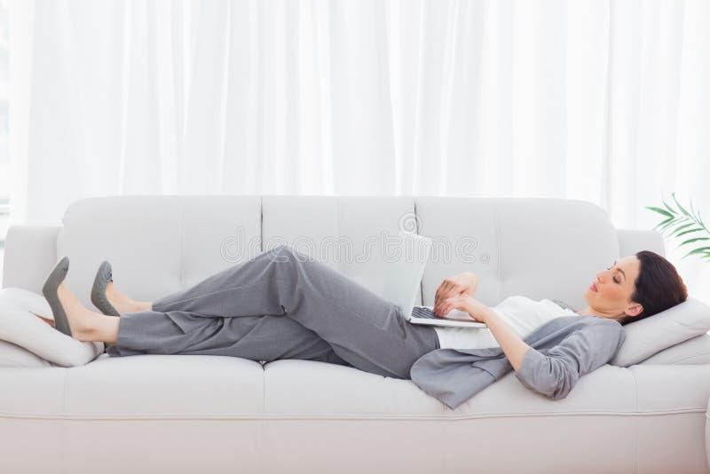 Businesswoman Using Her Laptop Lying On Sofa Stock Photos