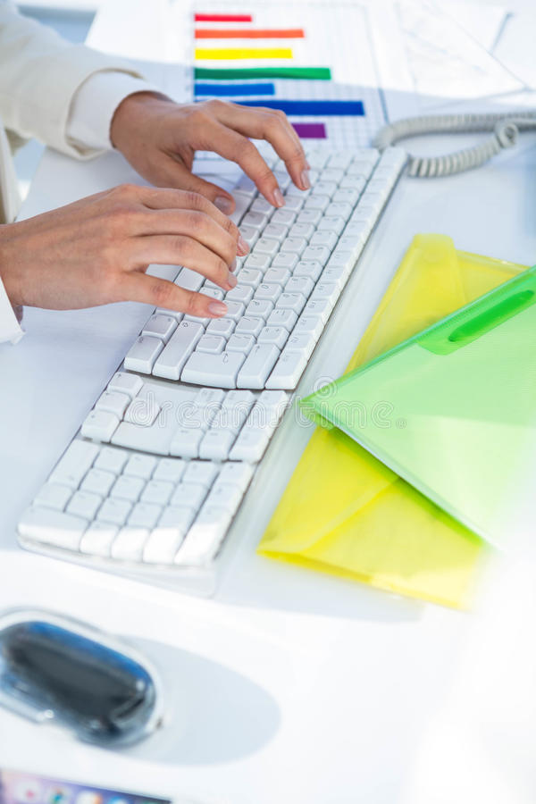Businesswoman using her pc with documents. At the desk in work stock photo