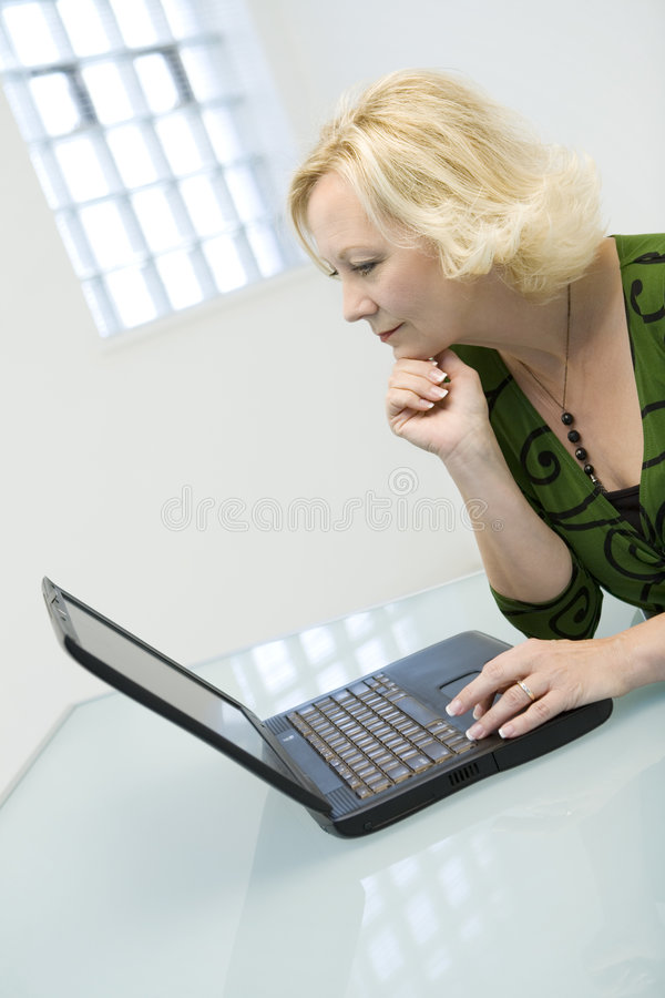 Businesswoman using laptop. A view of a middle aged businesswoman sitting at a desk, working on a laptop computer stock image