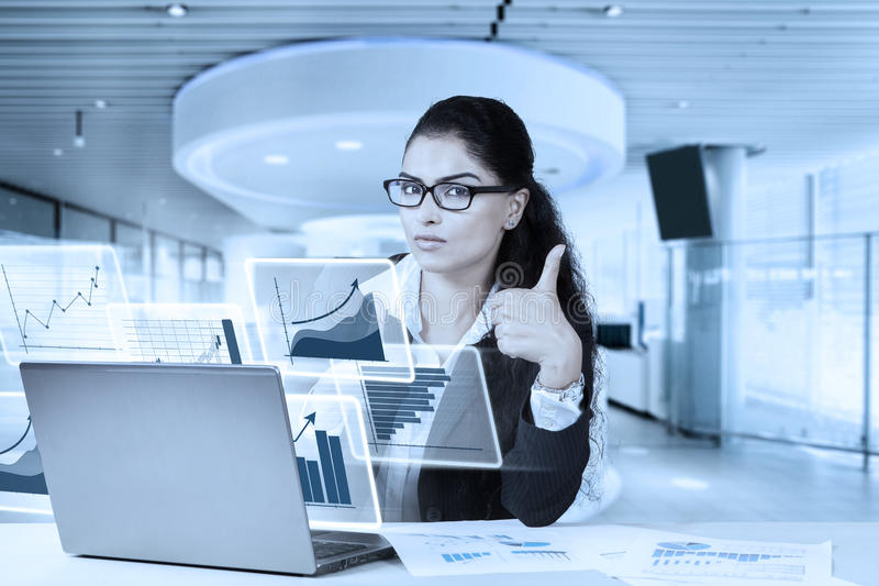 Businesswoman using laptop and showing thumb up. Portrait of beautiful businesswoman using laptop while showing thumb up at the camera with laptop and paperwork royalty free stock images
