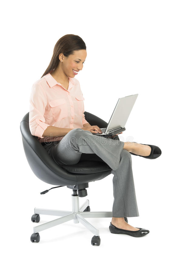 Businesswoman Using Laptop While Sitting On Office Chair