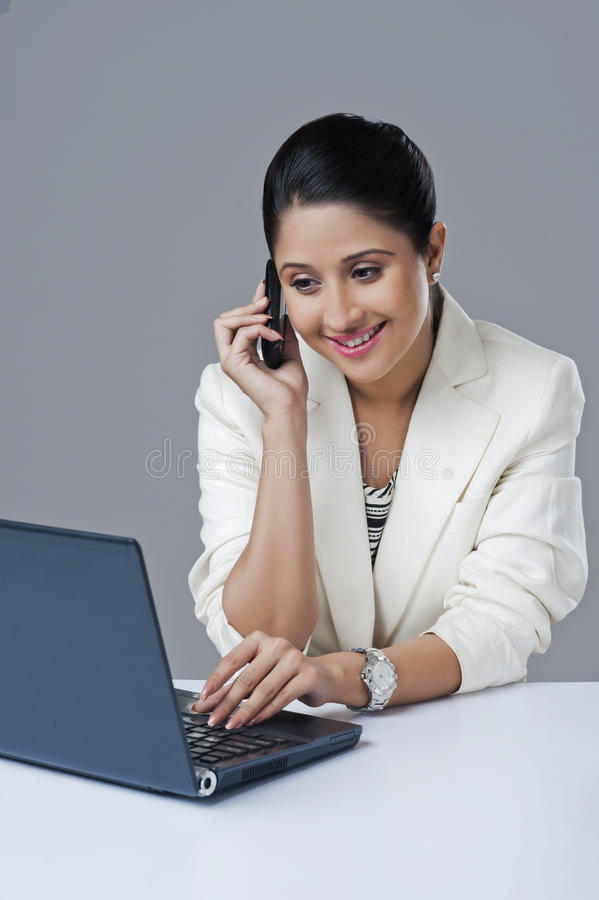 Businesswoman using laptop and talking on a mobile phone royalty free stock images
