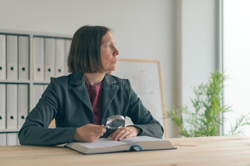 Businesswoman using magnifying glass to read the book royalty free stock photos