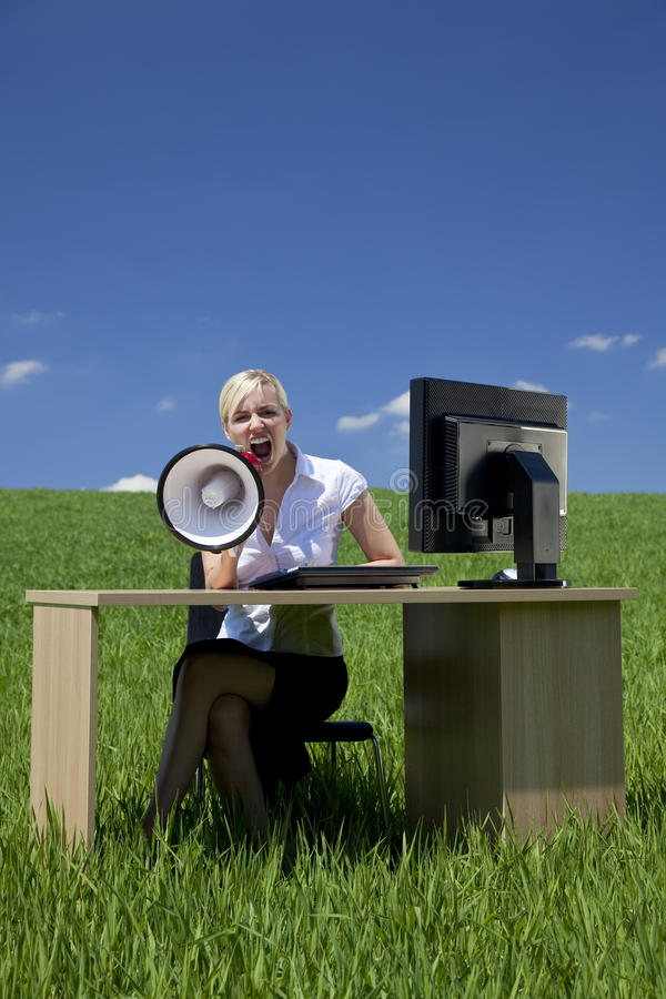 Businesswoman Using Megaphone In A Green Field. Business concept shot of a beautiful young woman sitting at a desk using a megaphone in a green field with a stock image