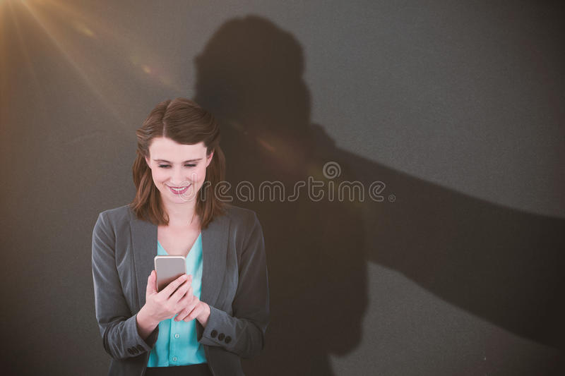 Composite image of businesswoman using mobile phone. Businesswoman using mobile phone against grey stock photography