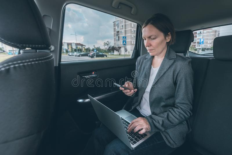 Businesswoman using mobile phone and laptop computer in car stock image