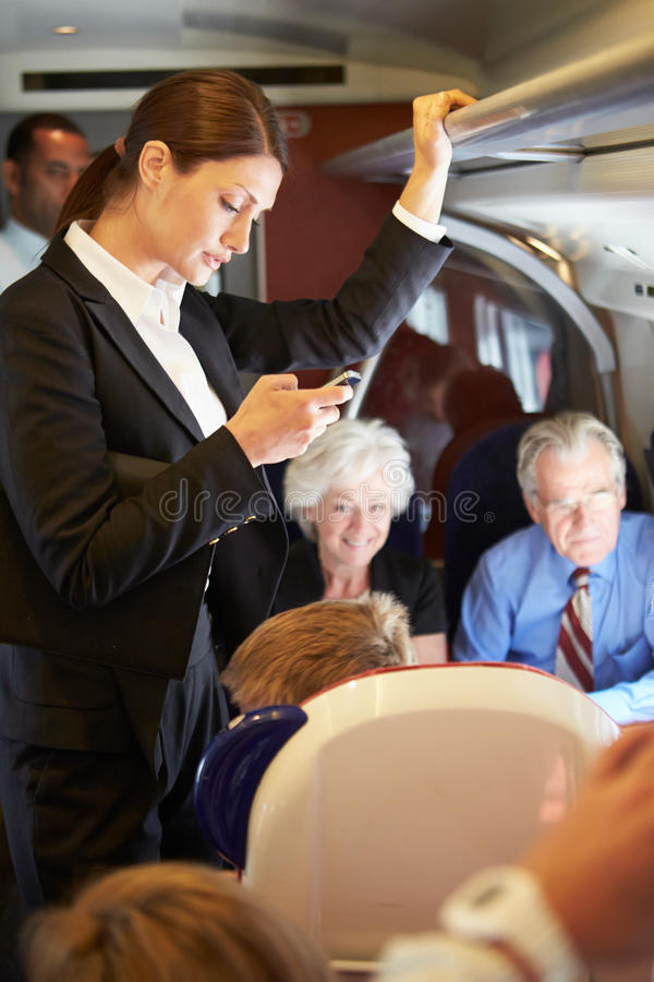 Free Businesswoman Using Mobile Phone On Busy Commuter Train Royalty Free Stock Photo - 33574645
