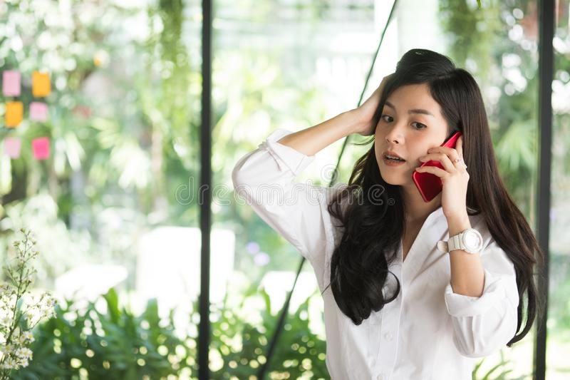 businesswoman using mobile phone at workplace. startup woman working at office. young female entrepreneur talk on smart phone. stock photos