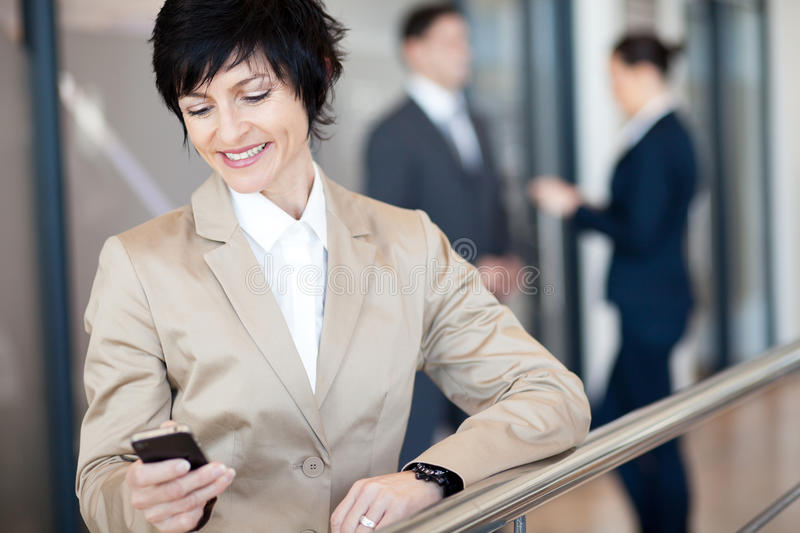 Businesswoman using smart phone. Middle aged businesswoman using smart phone stock image