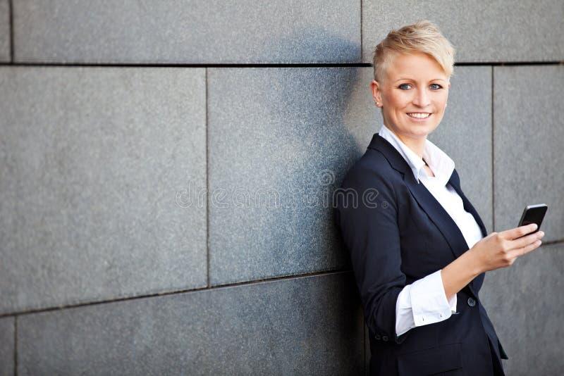 Businesswoman using smart phone. Confident businesswoman using smart phone royalty free stock photo