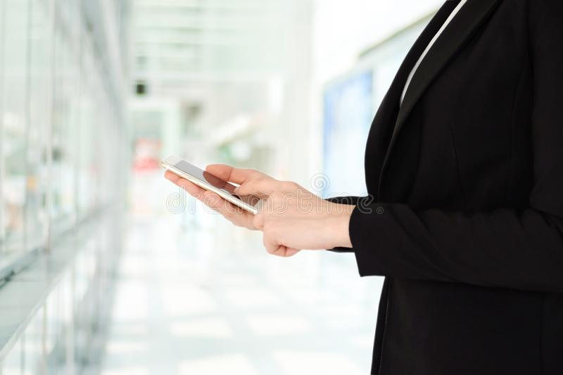 Businesswoman using smart phone over blur office background with copy space for text, people on phone, technology and lifestyle stock image