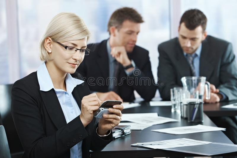 Businesswoman using smartphone in office. Smiling businesswoman using smartphone at office meeting with colleagues in background stock photos