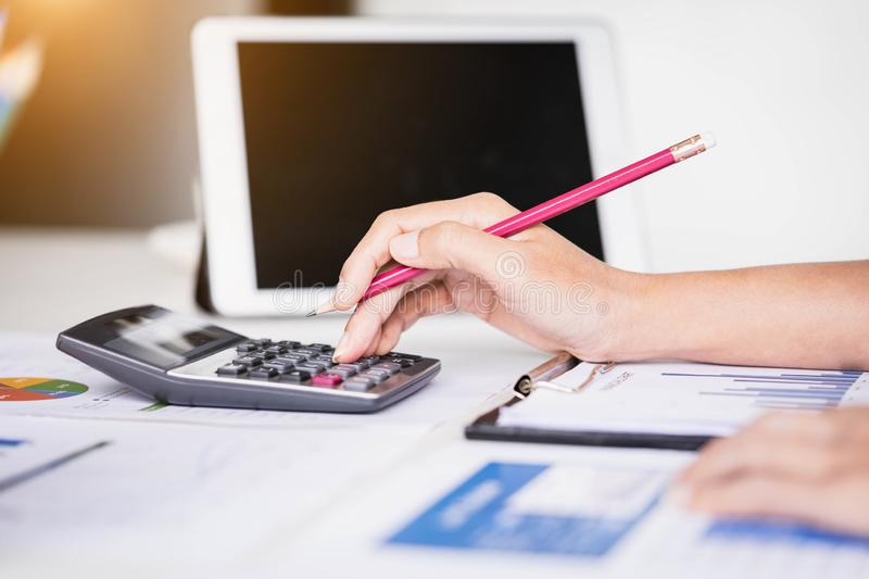 Businesswoman using tablet computer and calculator for calculating financial documents. Accounting,Finances and economy concept. stock images