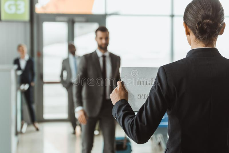 businesswoman waiting for partner with name sign on paper stock photography