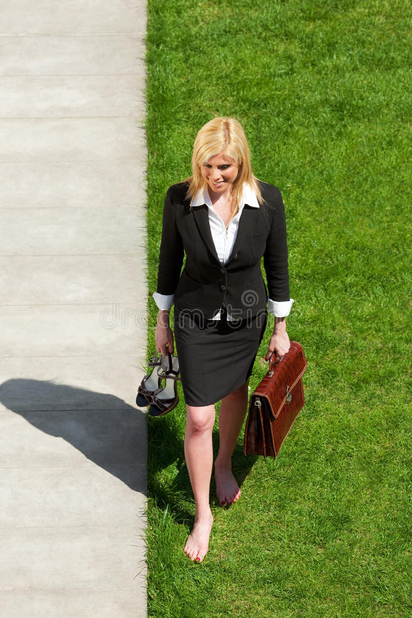 Businesswoman walking barefoot royalty free stock images