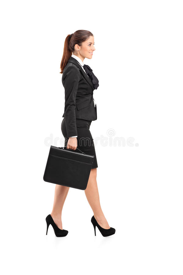 Businesswoman walking with a briefcase in her hand royalty free stock image