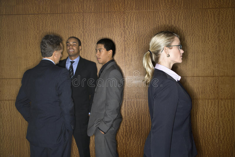 Businesswoman Walking by Businessmen. Businessmen of ethnic diversity talk in a group as a Caucasian businesswoman walks by. Horizontal shot stock images