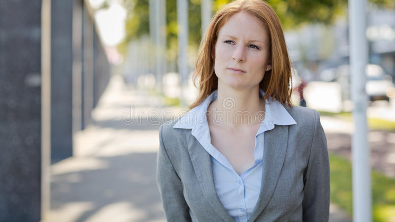 Businesswoman Walking in a City. Young businesswoman walks on a city street, copy space available stock images