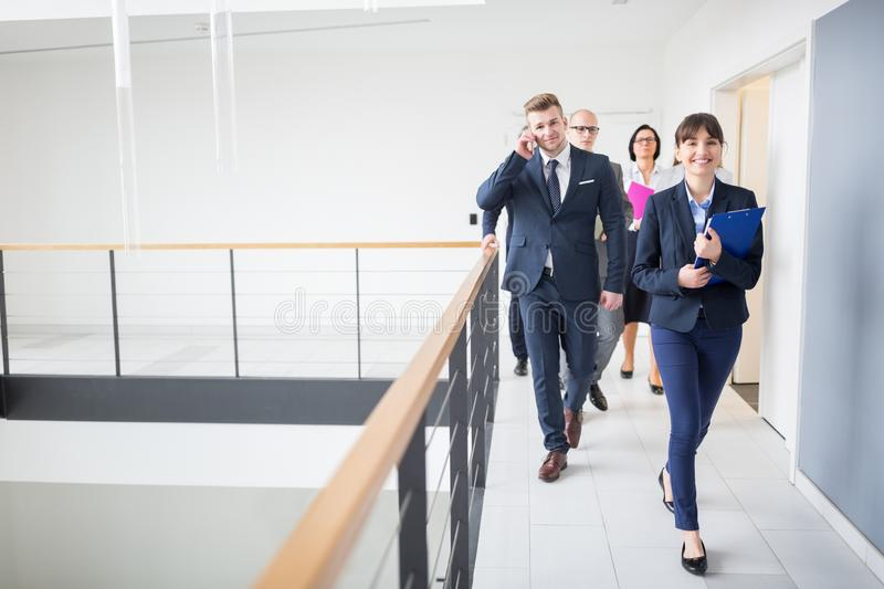 Businesswoman Walking On Corridor With Colleagues By Railing In Office stock photography