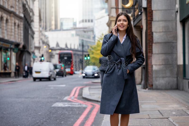 Businesswoman walking down the street in the City of London, UK stock image
