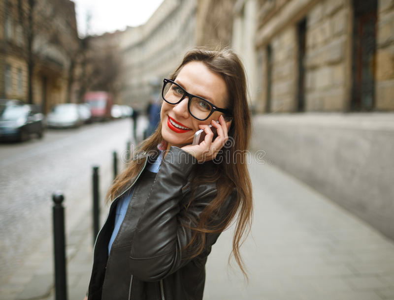 Businesswoman walking down the street while talking on smart phone. Happy smiling caucasian business woman busy royalty free stock images