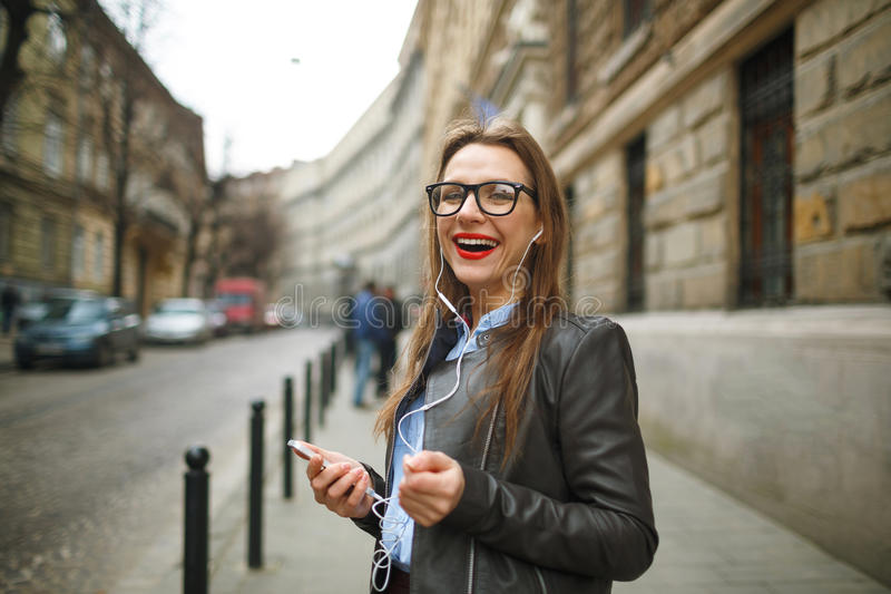 Businesswoman walking down the street while using the smart phon. E. Happy smiling caucasian business woman busy stock image