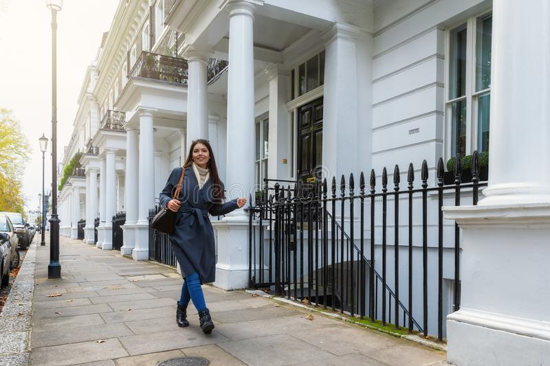 Businesswoman walking in front of Victorian Houses in London. Beautiful London businesswoman walking in front of white Victorian Houses in London stock image