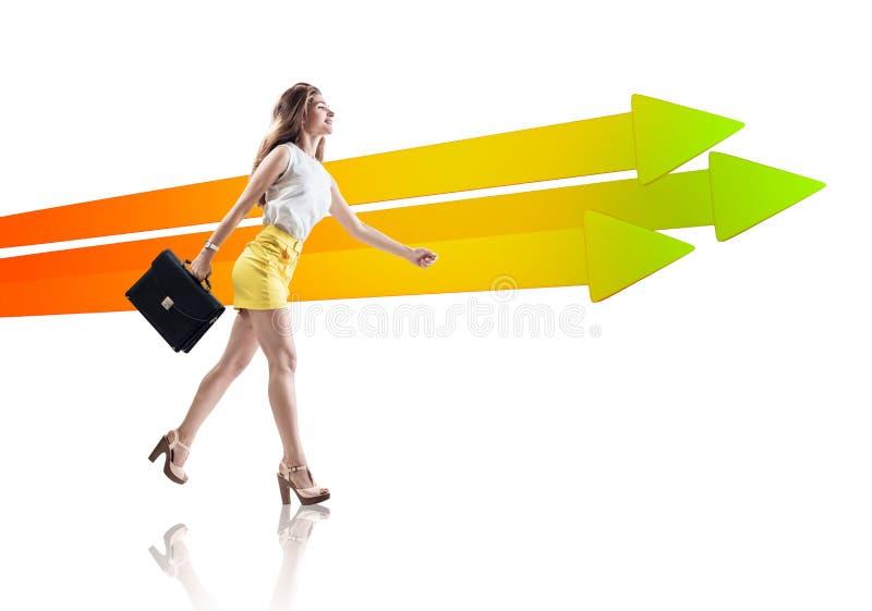 Businesswoman walking near big arrows. stock photo