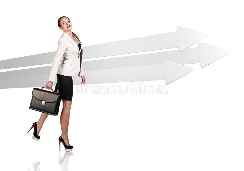 Businesswoman walking near big gray arrows. stock photos