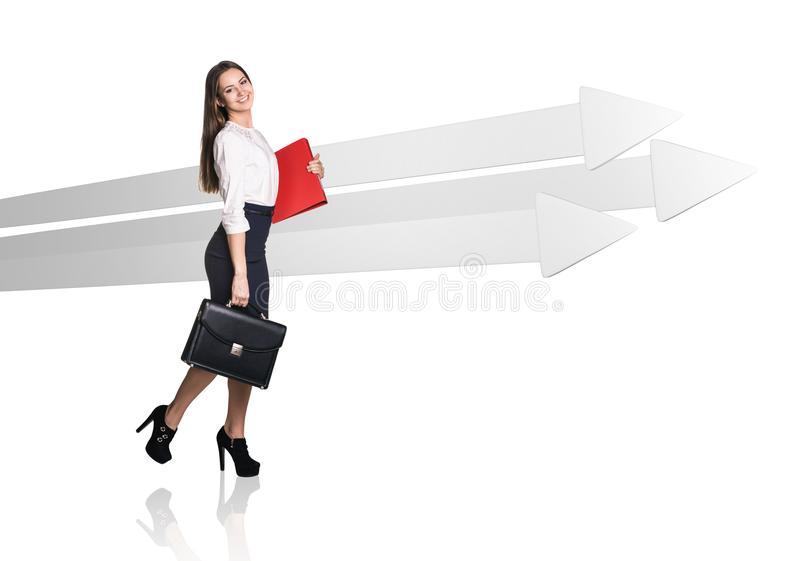 Businesswoman walking near big gray arrows. royalty free stock photography