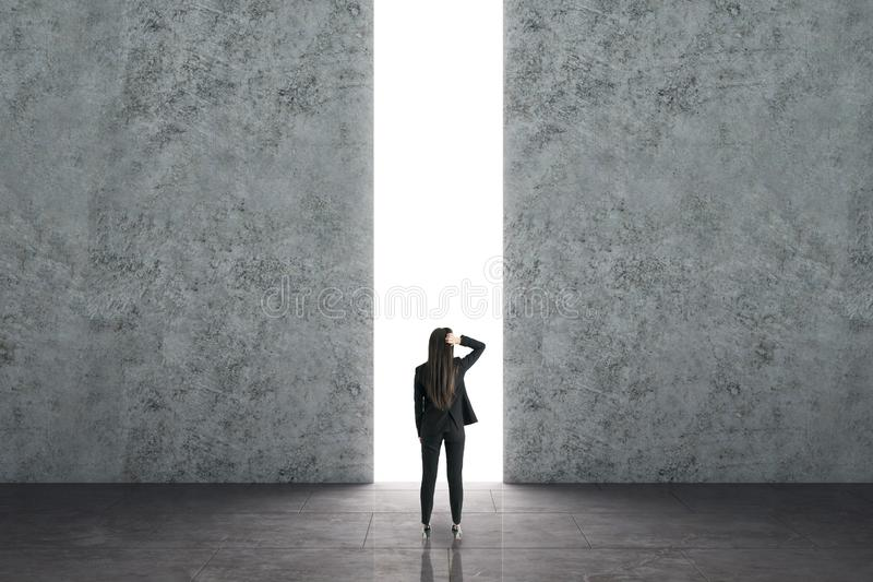 Opportunity and access concept. Businesswoman walking towards bright opening in concrete wall. Opportunity and access concept stock image