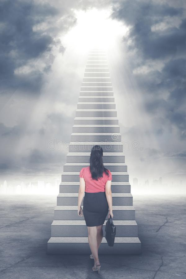 Businesswoman walking up staircase to door in sky with bright light shining down.  royalty free stock photo