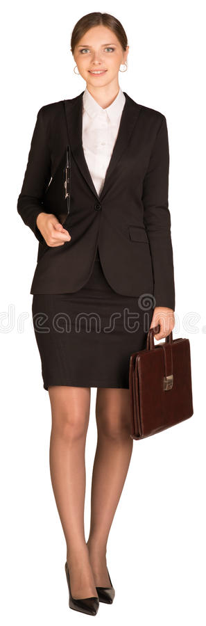 Businesswoman walks holding briefcase and paper stock photography