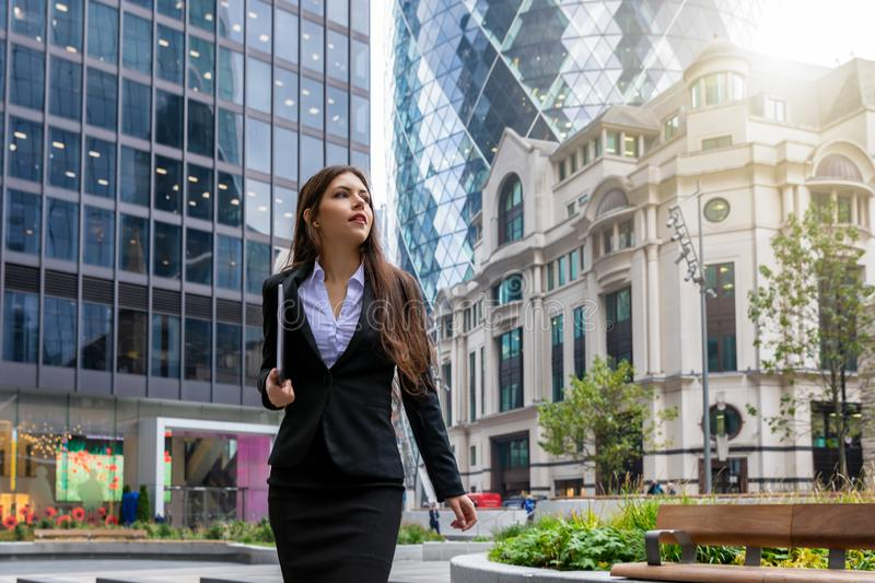 Businesswoman walks outdoors in financial district with a laptop in her hand. Confident, good looking businesswoman in corporate outfit walks outdoors in stock photography