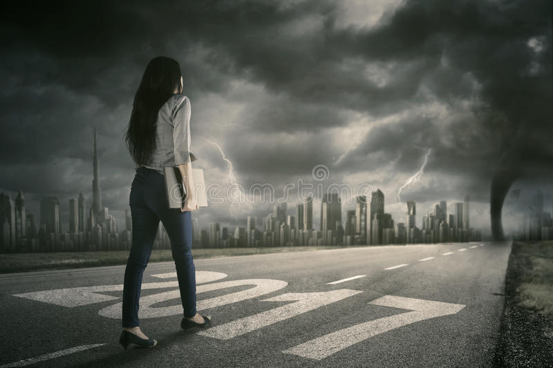 Businesswoman walks on street with hurricane. Rear view of young businesswoman walking on the road while carrying a laptop with number 2017 and hurricane royalty free stock photo