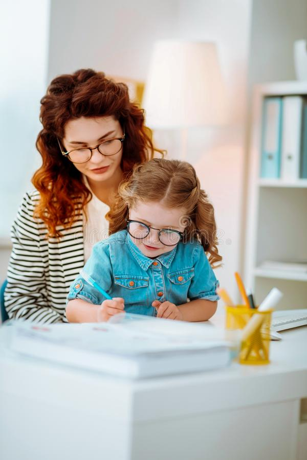 Businesswoman watching her funny daughter in glasses painting royalty free stock photos