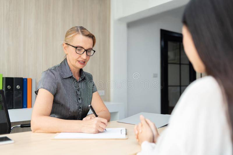 Businesswoman talking with female employee. stock photography