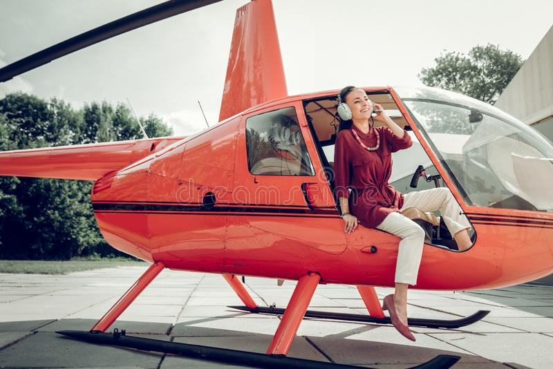 Businesswoman wearing beige trousers leaving little private helicopter royalty free stock images