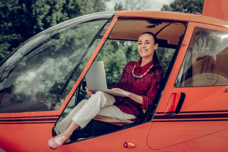 Businesswoman wearing beige trousers sitting in private helicopter stock photography