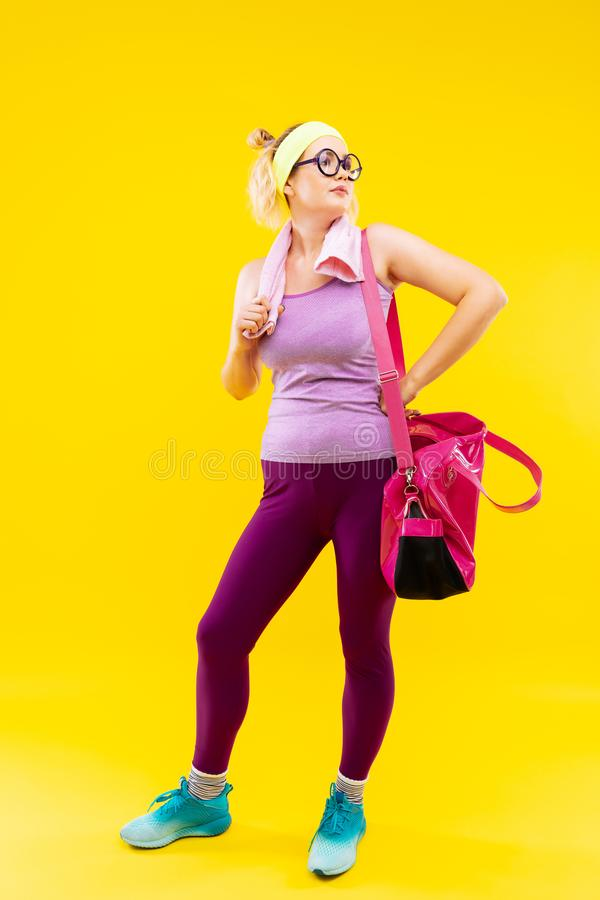 Businesswoman wearing bright clothes leaving gym after sport time stock images
